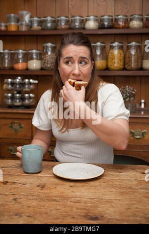 Eine Frau in ihren 30er Jahren, die ein Stück Kuchen isst - Stockfoto