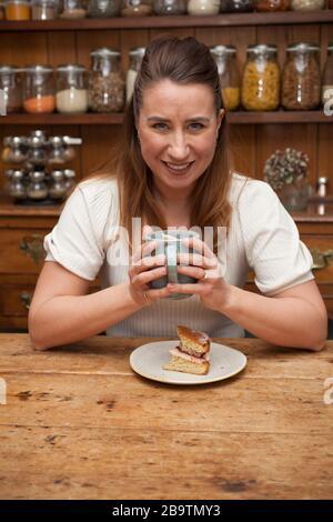 Eine Frau in ihrer Landesküche mit Kaffee und Kuchen - Stockfoto