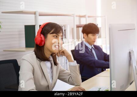 Eine asiatische Geschäftsfrau hört Musik von seinen Kopfhörern im Büro und die Männer sitzen ernst. - Stockfoto
