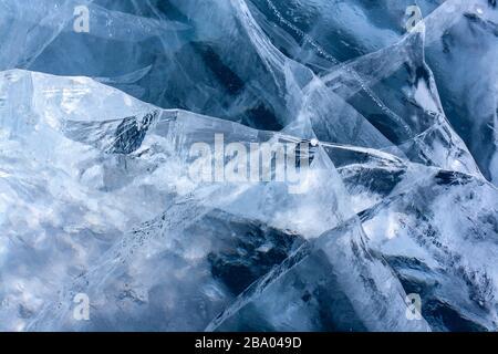 Wunderschönes knacktes Eis auf dem See. Klares blaues Eis mit weißen Rissen. Horizontal.