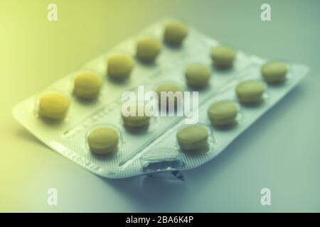 Blister mit gelben Vitaminen oder Pillen auf dem Tisch, ein Vitamin wird bereits gegessen, Nahaufnahme, Seitenansicht. Stockfoto