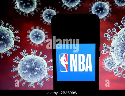 In dieser Abbildung wird ein Logo der National Basketball Association (NBA) auf einem Smartphone mit einem Computermodell des Coronavirus COVID-19 im Hintergrund angezeigt. - Stockfoto