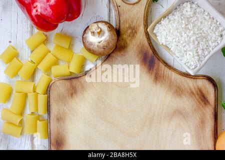 Küchenbrett umgeben von Gemüse und Gewürzen - Stockfoto