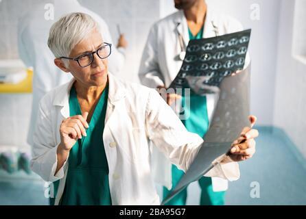 Ärzte diskutieren die Diagnose des Patienten und betrachten Röntgenaufnahmen in einem Krankenhaus - Stockfoto