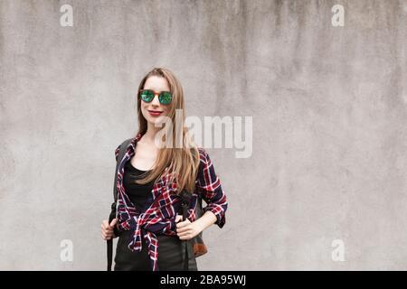 Junges schönes Mädchen auf dem Hintergrund der grauen Betonwand. Sie lächelt und schaut auf die Kamera. - Stockfoto
