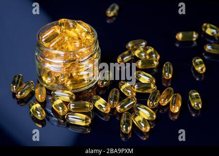 Omega Fischöl mildert Nahrungsergänzungsmittel im Mixbecher. Gesundes Leben und Gesundheitskonzept des Herzens. Konzentrieren Sie sich auf die Tabletten im Mixbecher - Stockfoto