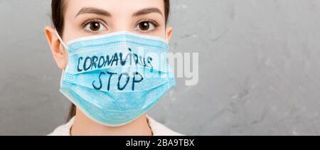 Portrait einer Frau in medizinischer Maske mit STOP-Coronavirus Text im grauen Zementhintergrund. Coronavirus Konzept. Atemschutz. - Stockfoto