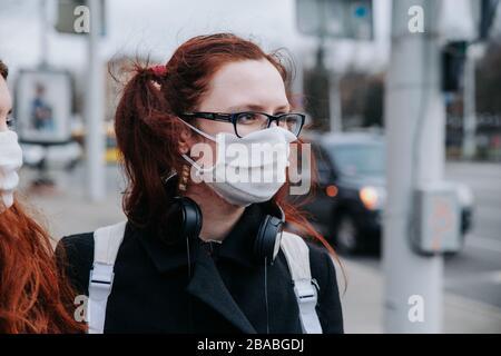 Junge Europäische Frau im Balckmantel, schützende Einwegmaske in der Straße der Stadt - Stockfoto
