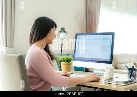Junge asiatische Geschäftsfrau, die ihre E-Mails von zu Hause aus überprüft, um Viren zu schützen und sich um ihre Gesundheit von COVID-19 zu kümmern. Arbeiten zu Hause - Stockfoto