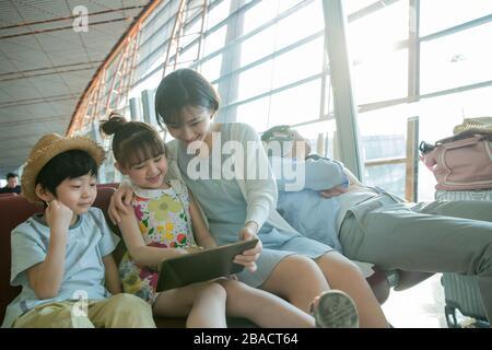 Die junge Mutter und die Kinder sehen sich das Tablet in der Flughafenlounge an - Stockfoto