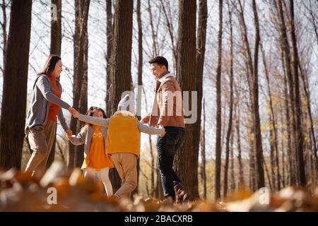 Glückliche Familie Hand in Hand, um draußen zu spielen - Stockfoto
