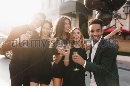 Schwarzer Mann mit afrikanischer Frisur, der Glas Wein hält und mit einem fröhlichen Lächeln auf die Kamera blickt. Brünette Frau im trendigen Kleid, die Champagner genießt und sich beim Fotoshoot mit dem Freund umarmt. - Stockfoto
