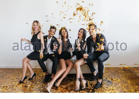 Lachender, schwarzhaariger Kerl in schwarzen Schuhen, der beim Fotoshoot mit Freunden goldene Konfetti ausplaudert. Innenfoto von Mädchen mit Gläsern Wein auf dem Sofa mit Freunden. - Stockfoto