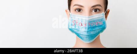 Porträt einer hübschen Frau, die eine medizinische Maske trägt, mit Text zu Hause bei weißem Hintergrund bleiben. Selbstisolierungskonzept für Coronavirus. Atemschutz. - Stockfoto