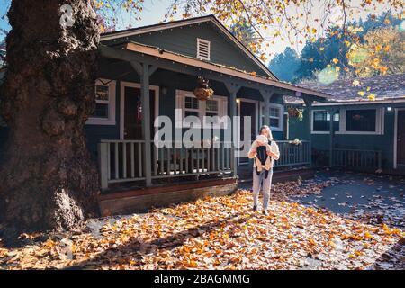 Eine Frau mit Kind steht neben einem Haus auf gelben Blättern Stockfoto
