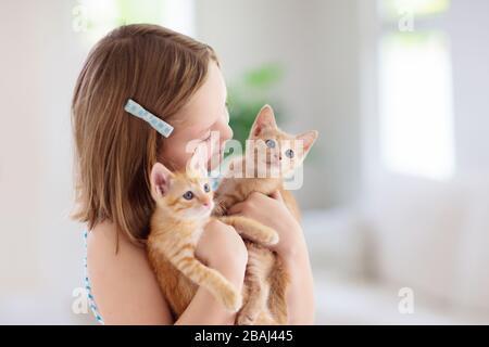 Kind, das eine Babykatze hält. Kinder und Haustiere. Kleines Mädchen umarmt niedliches kleines Kätzchen zu Hause. Haustier in der Familie mit Kindern. Kinder mit Haustieren.