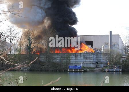 Remseck, Deutschland. März 2020. Bei einem Brand vor einem Recyclingzentrum am Neckar steigen dicke schwarze Rauchwolken auf. Der Müll vor der Halle habe Feuer gefangen, sagte eine Polizeisprecherin. Das Feuer war bis auf einige kleinere Flammen fast gelöscht. Über die Brandursache oder Verletzte wurde zunächst nichts gesagt. Kredit: Karsten Schmalz / dpa / Alamy Live News - Stockfoto