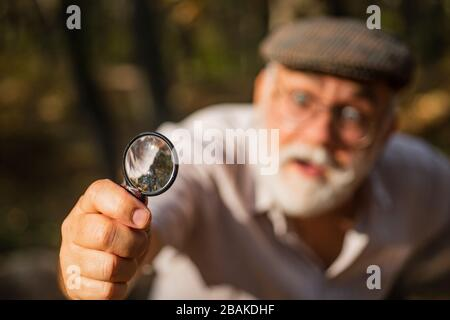 Selektiver Lupenfokus. Forschung und Entdeckung. Vergrößerungsleistung. Der alte Mann verwendet Lupe in der Natur. Sehsinn. Objektiv und optisches Werkzeug. Der alte Mann blickt durch die runde Linse im Freien.
