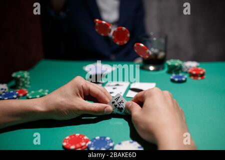 Professionelles Pokerspiel. Grüner Pokertisch mit zwei Spielen. Der Pokerspieler macht einen Einsatz, indem er Chips auf den Tisch wirft - Stockfoto