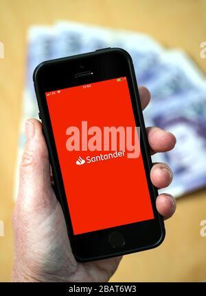 Eine Frau, die die Santander Bank-App auf einem Handy verwendet. (Nur Redaktionelle Verwendung) - Stockfoto