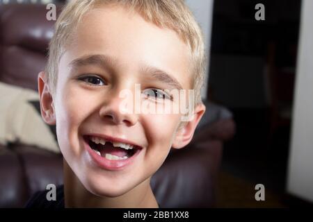 Ein Foto mit einem Kopfschuss aus der Nahaufnahme eines schönen jungen Jungen mit einem sehr lustigen Gesichtsausdruck und einfach albern. Er hat haselbraune Augen und blonde Haare. - Stockfoto