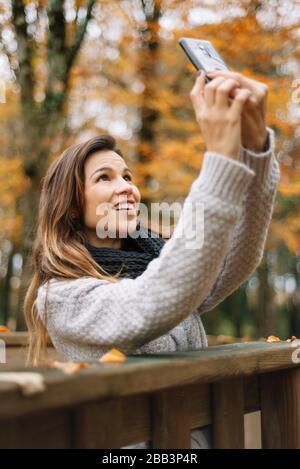 Schöne junge glückliche Frau, die selfie mit Smartphone im Herbstpark mitnimmt. Saison-, Technologie- und Personalkonzept.
