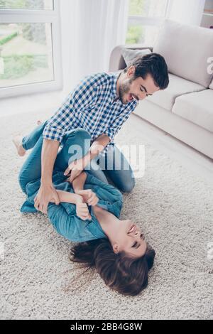 Aufgeregtes junges Paar töricht sich herum und spielt zuhause, auf einem gemütlichen beigen Teppich, mit lässigen Outfits, Lachen - Stockfoto