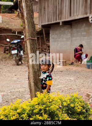 Ein Kind spielt auf dem Sandplatz neben der Straße - Stockfoto
