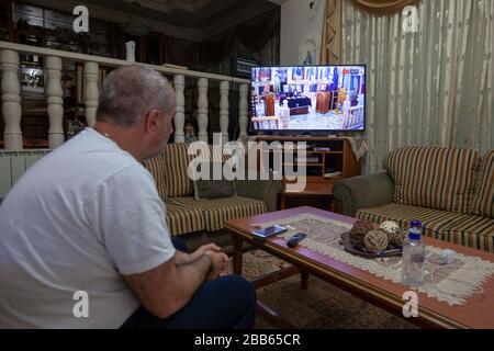 """(200330) -- BETHLEHEM, 30. März 2020 (Xinhua) -- EIN Palästinenser beobachtet am 29. März 2020 eine Live-Fernsehübertragung der Sonntagsmesse von einer orthodoxen Kirche in Beit Sahour nahe der Westjordanstadt Bethlehem. Zum ersten Mal besuchte Raed al-Atrash, ein 54-jähriger palästinensischer Mann aus der Westjordanstadt Bethlehem, mit seiner Familie die Sonntagsmesse über eine Live-Fernsehübertragung, da die Kirchen im Rahmen der Vorsichtsmaßnahmen gegen die Verbreitung des Romans Coronavirus geschlossen sind.TO GO WITH """"Feature: Christen in Palästina nehmen an Live-gebeten als Kirchen in der Nähe von Coronavirus Fears' (Foto von Luay Stockfoto"""