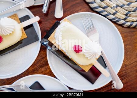 Mini-Mousse-Gebäckdessert mit weißer Schokolade. Kuchen in Form von Eiscreme auf dem Stock - Stockfoto