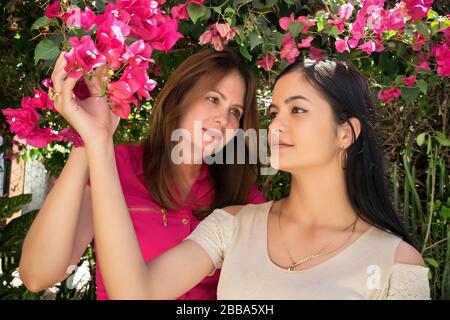 Eine kubanische Mutter mittleren Alters im Garten mit ihrer schönen jungen Tochter. - Stockfoto
