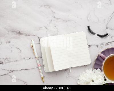 Draufsicht Bild des geöffneten Notebooks mit leeren Seiten und Kaffeetasse auf dem Hintergrund des marmornen Mottle-Tisches mit Copyspace, bereit zum Hinzufügen oder Verspotten. Noch l - Stockfoto