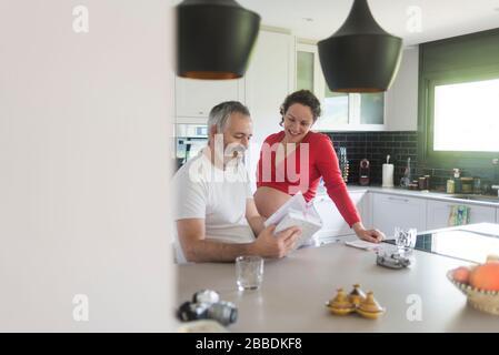 Lächelndes Paar, das ein Buch in der Küche berät. - Stockfoto