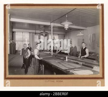 Anfang 1900 Foto von Männern auf der Arbeit im Schneideraum eines Bekleidungsunternehmens, das Muster verwendet und Wollanzüge aus Tweed, ca. 1930er Jahre, wahrscheinlich Norwich, England, Großbritannien, anfertigte - Stockfoto