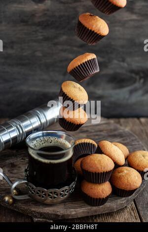 Fliegende Muffins fallen in eine Tasse Kaffee. Fliegende Lebensmittel. Stockfoto