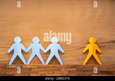 In Papierform werden die menschlichen Figuren getrennt, indem zwischen ihnen ein breiter Raum auf Holzhintergrund und ein soziales Distanzierungskonzept während des COVID-19-Virusausbruchs liegt - Stockfoto