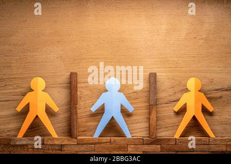 Menschliche Figuren, die in Papierform geschnitten sind, werden durch Holzblöcke auf Holzhintergrund getrennt, soziale Distanzierung während des COVID-19-Virus-Outbreak-Konzepts mit Platz für Kopien - Stockfoto