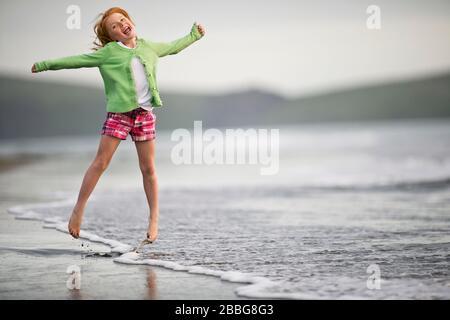 Porträt eines glücklichen jungen Mädchens, das bei Ebbe am Strand spielt - Stockfoto