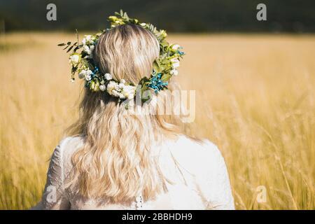 Rücken der jungen Frau in einem weißen Kleid im Boho-Stil mit einem Blumenkranz im Sommer auf dem Feld. Stockfoto