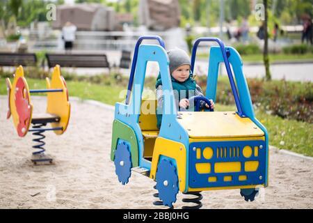 Kleiner Junge, der in einem Holzwagen auf dem Spielplatz sitzt. - Stockfoto