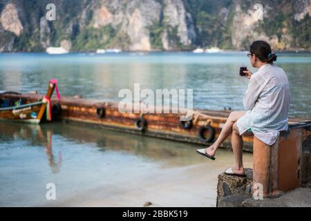 Frau trinkt Kaffee am Strand, Ko Phi Phi Insel, Thailand, Asien - Stockfoto