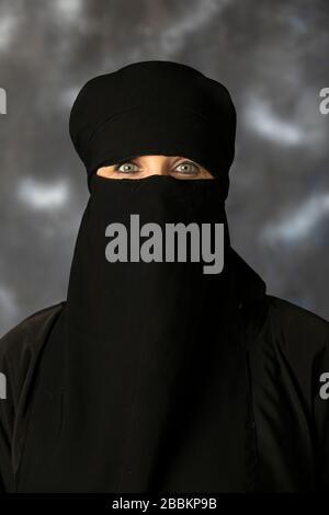 Porträt einer muslimischen Frau mit überdachtem Gesicht. Die Fotosession fand im Studio auf dunklem Hintergrund statt. Ein wunderschönes, junges 50-jähriges Mädchen. - Stockfoto