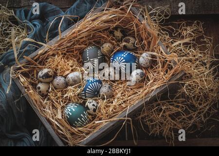 Wachteleier und bunte Wachs verzierte Hühnereier in einer Schachtel auf einem Heu. Osterkomposition in dunkler Stimmung Stockfoto