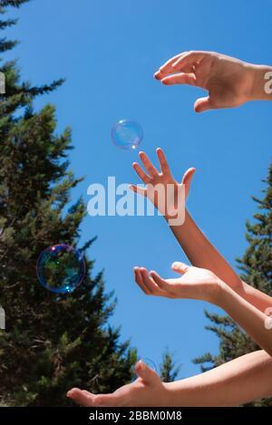 Seife bläst in den Händen der Kinder gegen einen blauen Himmel Stockfoto