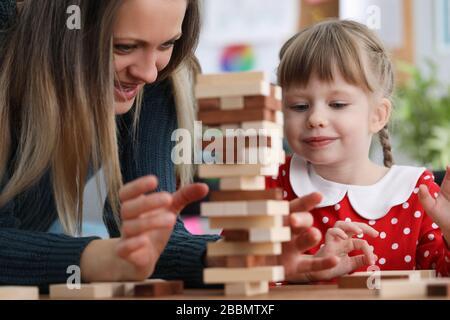 Mutter und Tochter bauen Holzblöcke auf