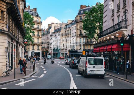 Menschen, die auf der Straße zwischen typischen pariser Gebäuden im Zentrum von Paris, Frankreich, spazieren gehen.