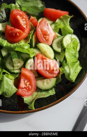 Frischer Detox-Salat im Sommer mit Tomaten, Gurke, Romain-Salat und Olivenöl auf Marmorgrund. Gesunde Ernährung für Veganer oder Vegetarier, Top V
