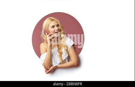 Bild einer jungen glücklichen Frau, die über weißem Hintergrund steht. Mädchen pep aus einem Loch in der Wand. Auf der Seite, um eine selfie auf dem mobilen Pho zu nehmen - Stockfoto
