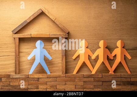 Blaue Papierausschnitte menschliche Figur in einem Holzblock, der nach Hause gebaut wurde, und drei weitere orangefarbene Papierausschnitte außerhalb des Holzhauses auf Holzrückenholz - Stockfoto