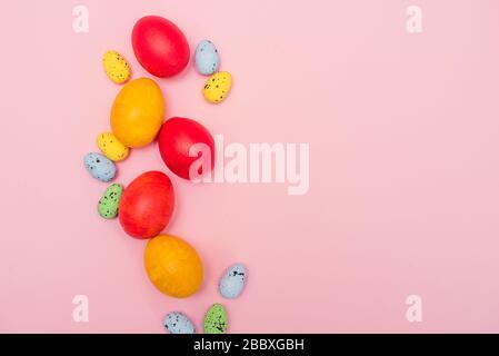 Ostereier auf pinkfarbenem Hintergrund. Rote und gelbe Hühnereier mit Pastell-Wachteleiern. Osterkarte. Kopierbereich. - Stockfoto